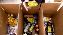 Anna Gonzales packs food into boxes at the Mental Health Center of Denver. April 3, 2020. (Kevin J. Beaty/Denverite)