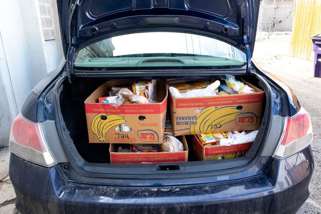 Evan Robertson's car is full of boxes from the Mental Health Center of Denver. April 3, 2020. (Kevin J. Beaty/Denverite)