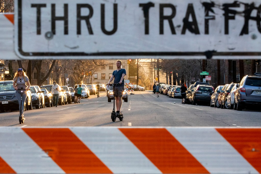 Kelsey Brown and Tyler Butler rides scooters down 11th Avenue while it's closed to cars and open to humans. April 7, 2020. (Kevin J. Beaty/Denverite)