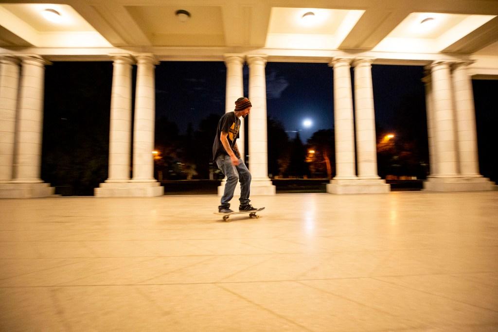 Travis Dunning skates in the Cheesman Park colonnade. April 7, 2020. (Kevin J. Beaty/Denverite)