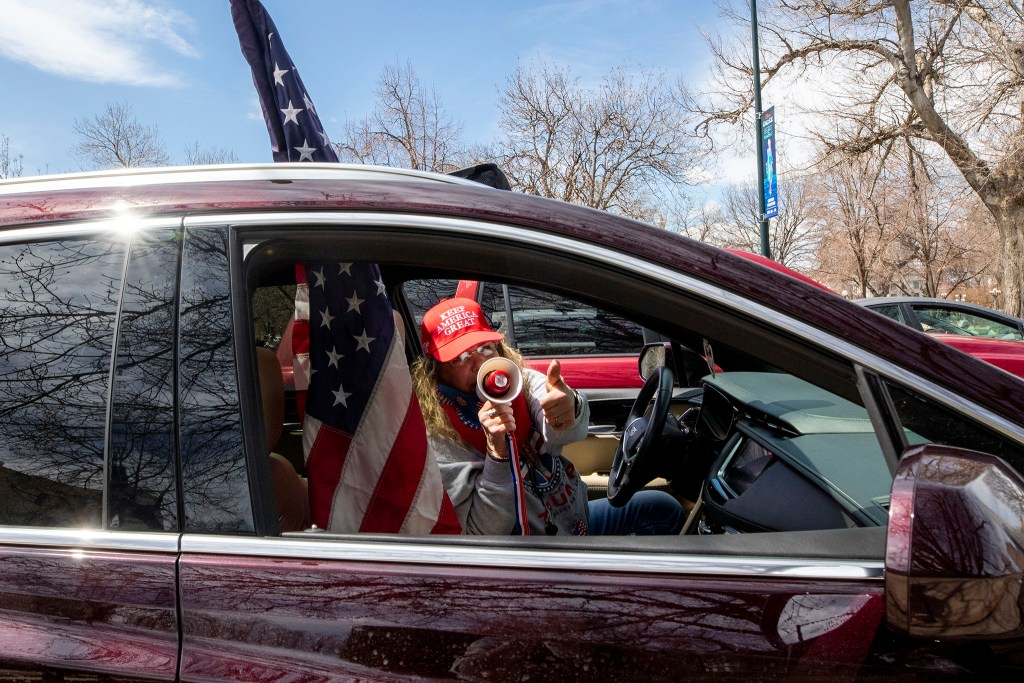 Jody Bacon yells through a megaphone from her car as protesters demand an end to Colorado's stay-at-home order. April 19, 2020. (Kevin J. Beaty/Denverite)