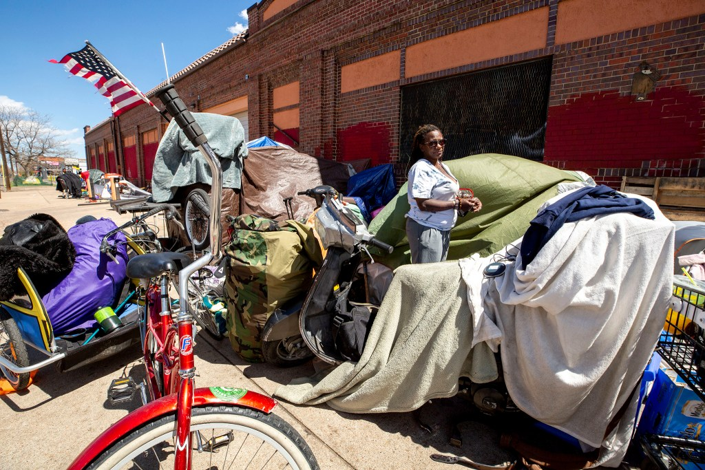 Kemish Anthony-Phillips packs her belongings on California Street ahead of an urban camping enforcement. April 28, 2020. (Kevin J. Beaty/Denverite)