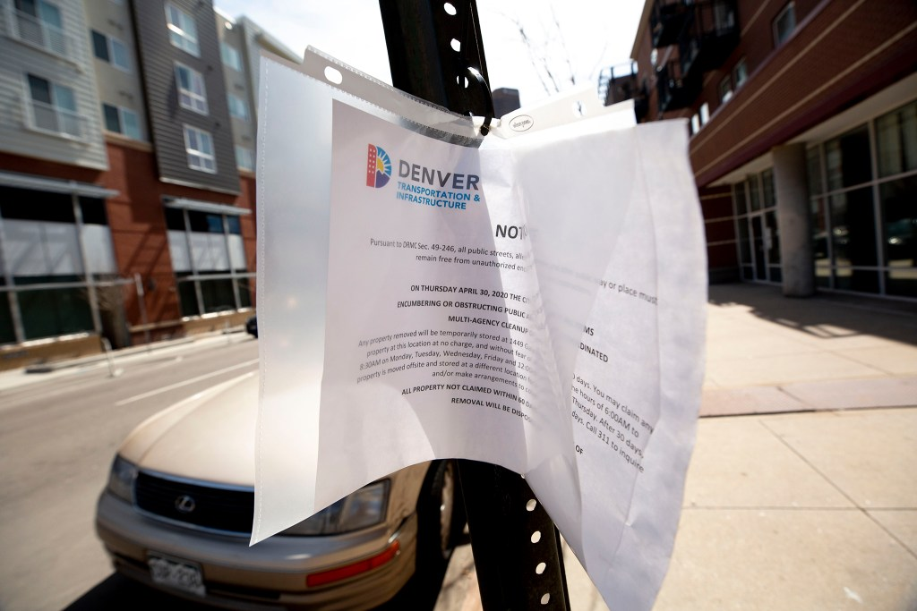 "A sign posted on Stout Street warning people camping nearby of a coming ""multi-agency cleanup."" April 28, 2020. (Kevin J. Beaty/Denverite)"