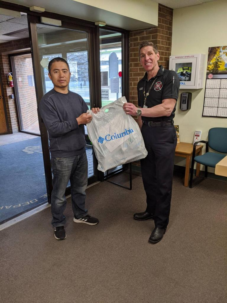 Xidong Sun presents some of the masks to Greg Pixley of the Denver Fire Department on Thursday. (Courtesy, DFD)