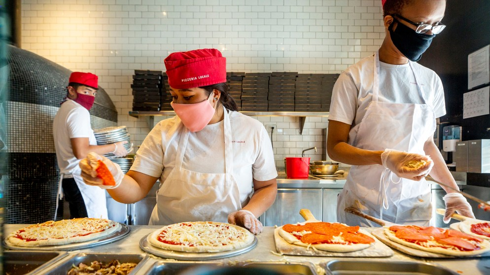 Johann Aneca, Leonela Flores and Kaci Rogers work behind masks at Pizzeria Locale on Broadway. May 7, 2020. (Kevin J. Beaty/Denverite)
