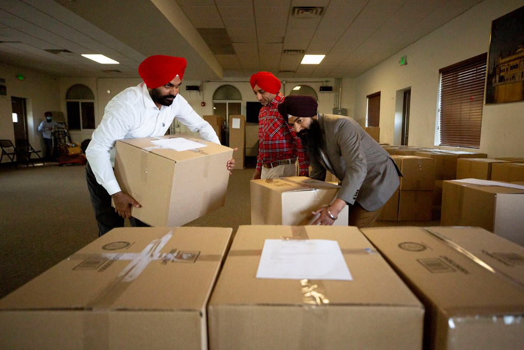 Kanwarbar Sandhu (left to right), Manjit Thiara and Davinder Sandhu grab boxes of snacks, packed here at Colorado Singh Sabha in Commerce City, that are bound for frontline workers across the state. May 8, 2020. (Kevin J. Beaty/Denverite)