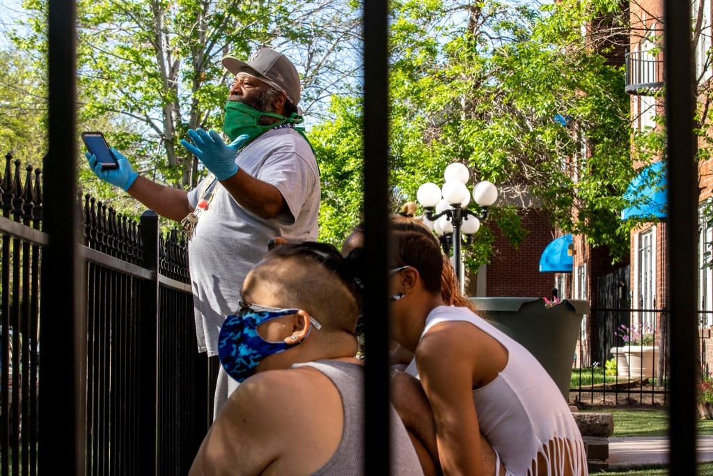 Johnnie Miles, a resident here on Washington Street, exchanges words with people camping outside of St. John's Episcopal Cathedral. Capitol Hill, May 20, 2020. (Kevin J. Beaty/Denverite)