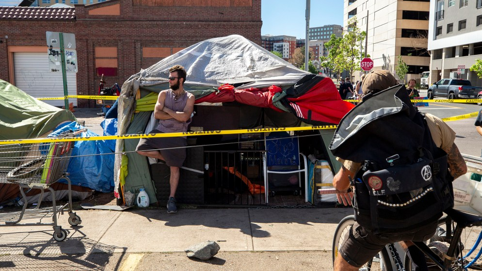 Dustin Fitzpatrick leans on his tent as authorities enforce a clean up of this encampment near the intersection of California and 21st Streets. May 27, 2020. (Kevin J. Beaty/Denverite)