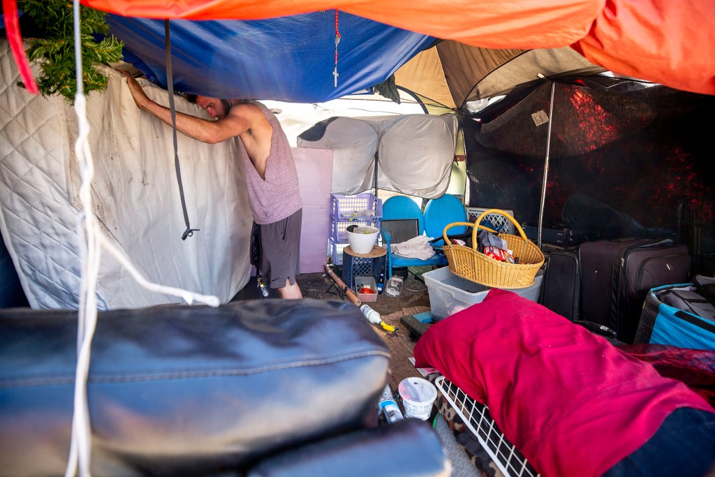 Dustin Fitzpatrick cleans up his tent after authorities offered him a stay at a local motel instead of jail time during an enforcement action near the intersection of California and 21st Streets. May 27, 2020. (Kevin J. Beaty/Denverite)