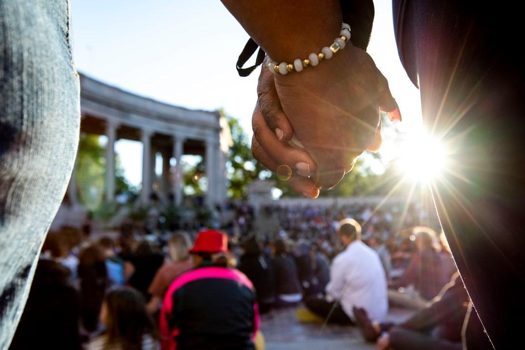 Melanie Crumb and Angela Jackson hold hands during a vigil for George Floyd at Civic Center Park. June 9, 2020. (Kevin J. Beaty/Denverite)
