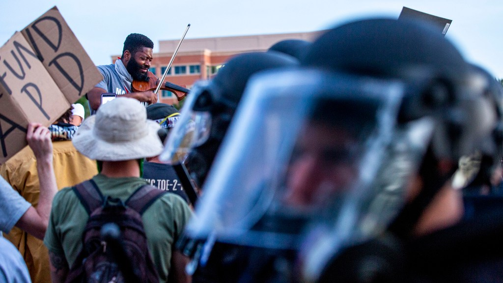 Jeff Hughes plays his violin as Aurora Police officers in riot gear keep protesters demanding justice for Elijah McClain off the municipal building lawn. June 27, 2020.