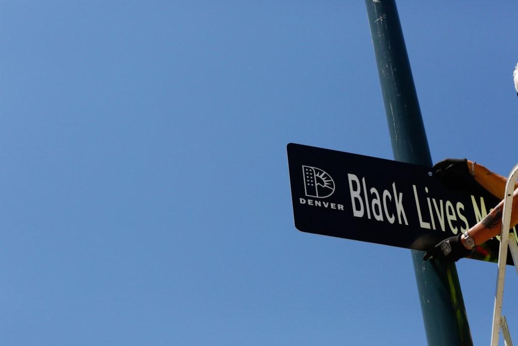 DENVER, JUNE 12: City workers hang a new street sign renaming Broadway Avenue to Black Lives Matter Boulevard at Civic Center Park in Denver, June 12, 2020. (Kevin Mohatt, Special to Denverite)
