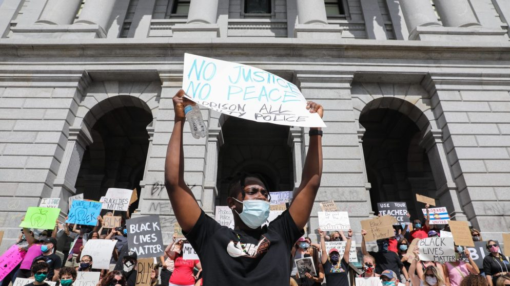 Elliot Sam, originally from Ghana and visiting Denver, helps lead a chant for educators opposing racism and police brutality and supporting Black Lives Matter at the state Capitol Thursday, June 11, 2020. (Hart Van Denburg/CPR)