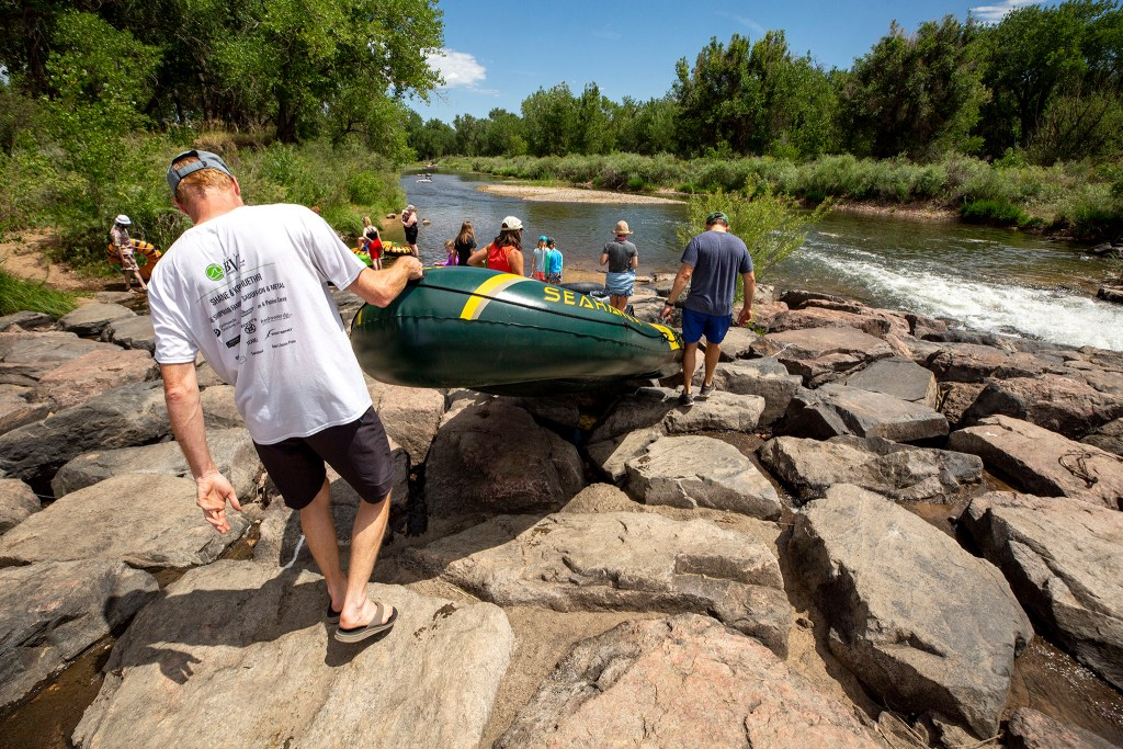 Intrepid rafters head into the South Platte River despite low levels here at Littleton's South Platte Park. July 18, 2020.