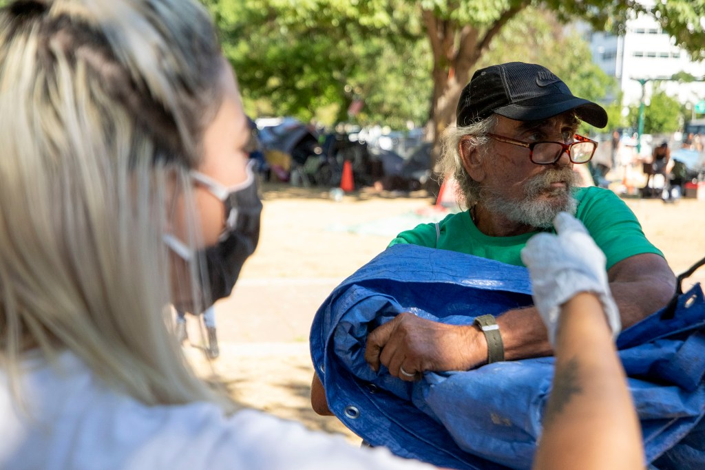 Steve Waring cleans up his camp, where he's lived for two months, as city officials conduct a forced cleanup of encampments here at Lincoln Park. July 29, 2020.
