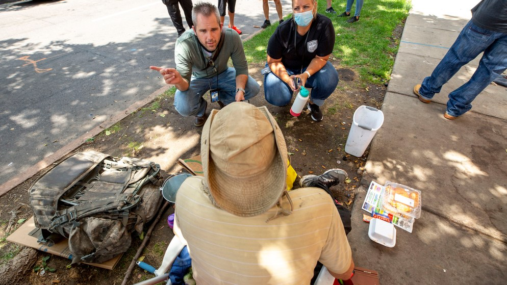 Mental Health Center of Denver workers Chris Richardson and Randi Edwards speak to Charles Gilmore on a sidewalk in North Capitol Hill. July 30, 2020.