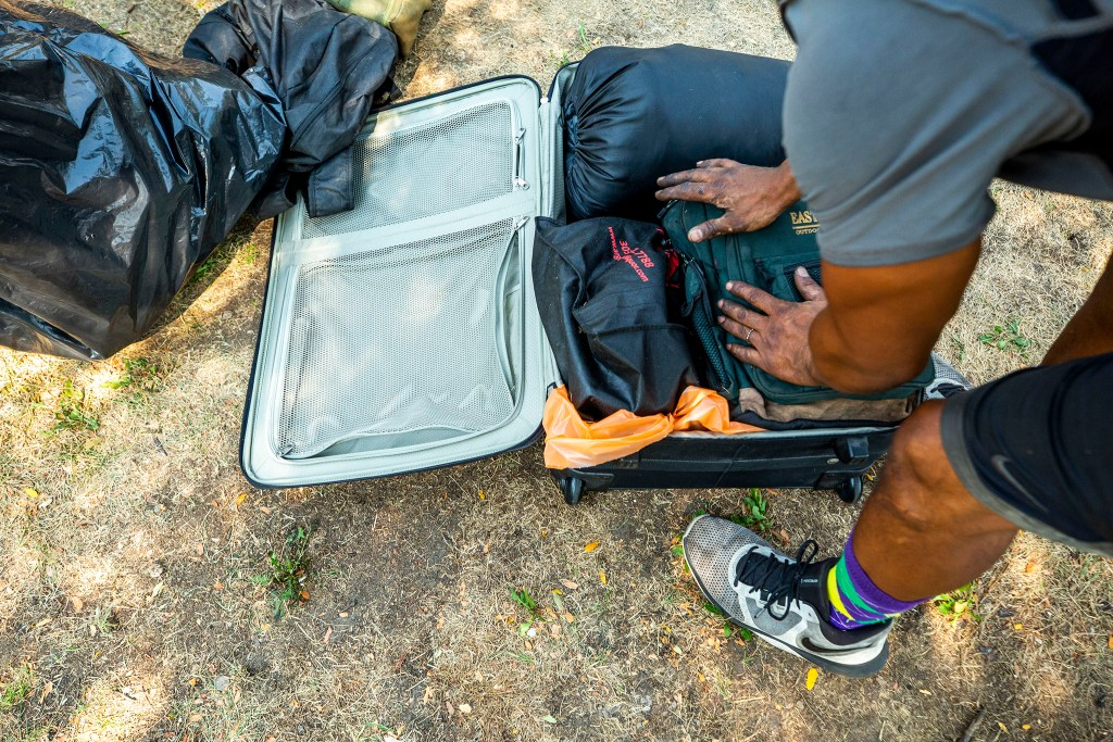 Marcio Johnson packs up his belongings during a forced cleanup of the encampment where he's been staying in front of Morey Middle School. Capitol Hill, Aug. 6, 2020.