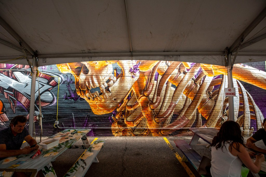 A mural by Smug One and Taste is partially obscured by dining tents in Denver Central Market's parking lot at 2669 Larimer St. in Five Points. Aug. 5, 2020.