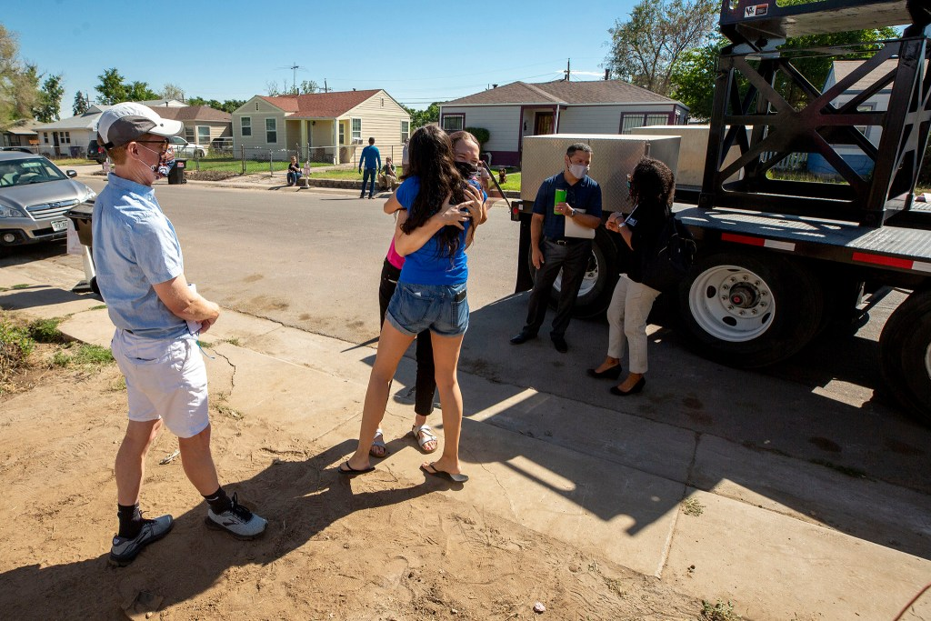 Nola Miguel, of the GES Coalition, embraces Councilwoman Candi CdeBaxa as a modular housing project goes up on land provided by the Colorado Community Land Trust in Elyria Swansea. Aug. 12, 2020.