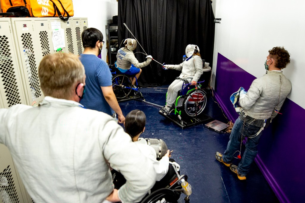 A crowd gathers to watch as Joe Greene and his former pupil, Hailey Bauer, spar on a parafencing rig at the Denver Fencing Center in Ruby Hill. Aug. 20, 2020.