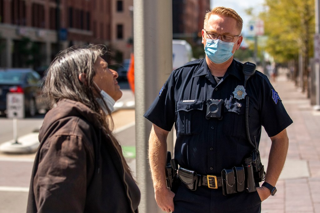 Denver Police Sgt. Brian Conover speaks with a woman who approached him on Wynkoop Street by Union Station to talk about government surveillance. Sept. 1, 2020.