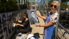 Stella Yu holds a picture of Gary Eloriaga, who died from COVID-19 in March. He will be memorialized here ouside of the Redline Contemporary Art Center as part of the COVID Walls project. Sept. 3, 2020.