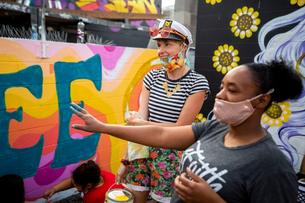 Lindee Zimmer (left) and Latifah Bannon chat by the mural they're working on together during CRUSH Walls 2020 at the Denver Central Market on Larimer Street. Sept. 18, 2020.