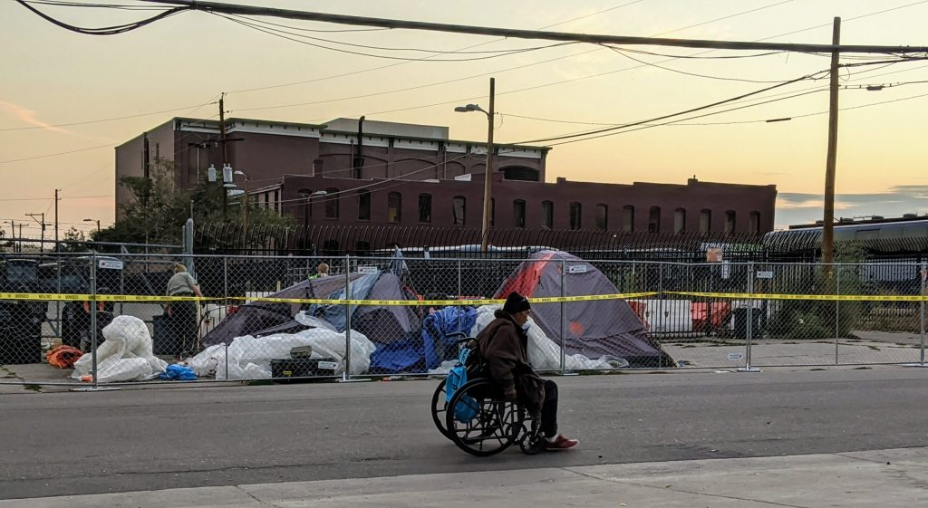Gary Martinez passes people dismantling tents along Arapahoe Street on Sept. 22, 2020.
