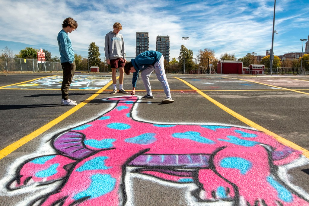 Doug Campbell (left to right), Jasper Rich and Zach Lawton finish up Lawton's painted parking space at East High School. Oct. 16, 2020.