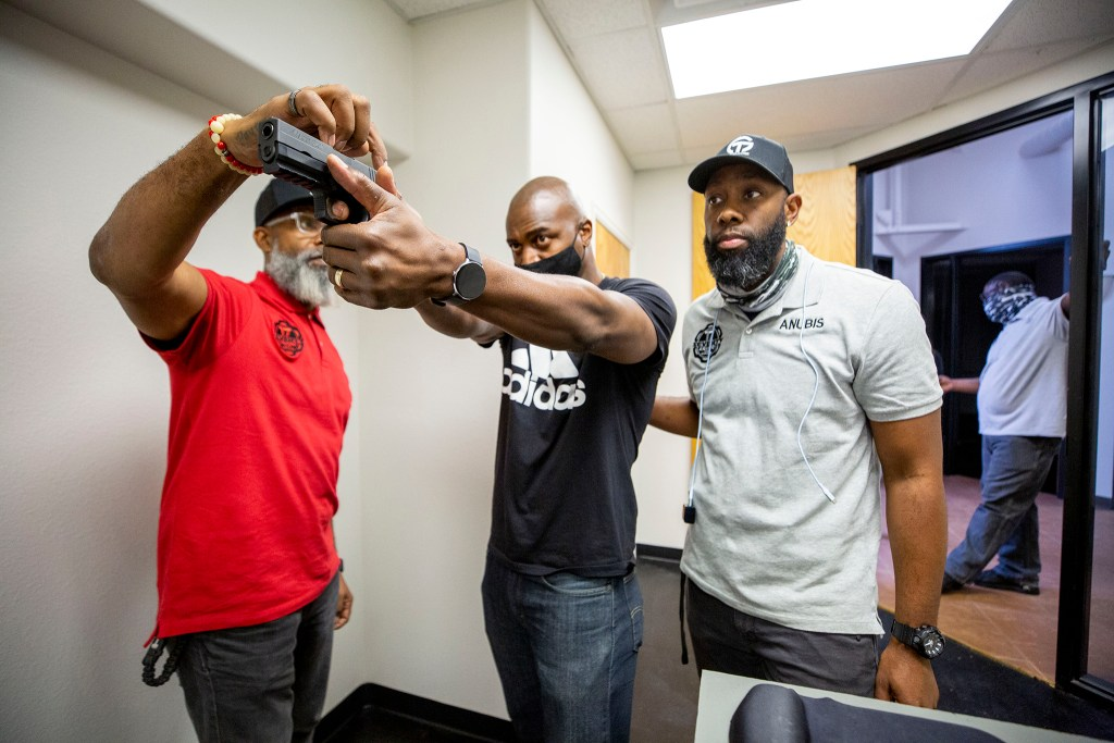 """Instructors Shawn McWilliams (left) and Anubis Haru work with Eric Hill inside 17 Seventy Armory and Gun Club's """"virtual"""" range in Five Points. Oct. 17, 2020."""