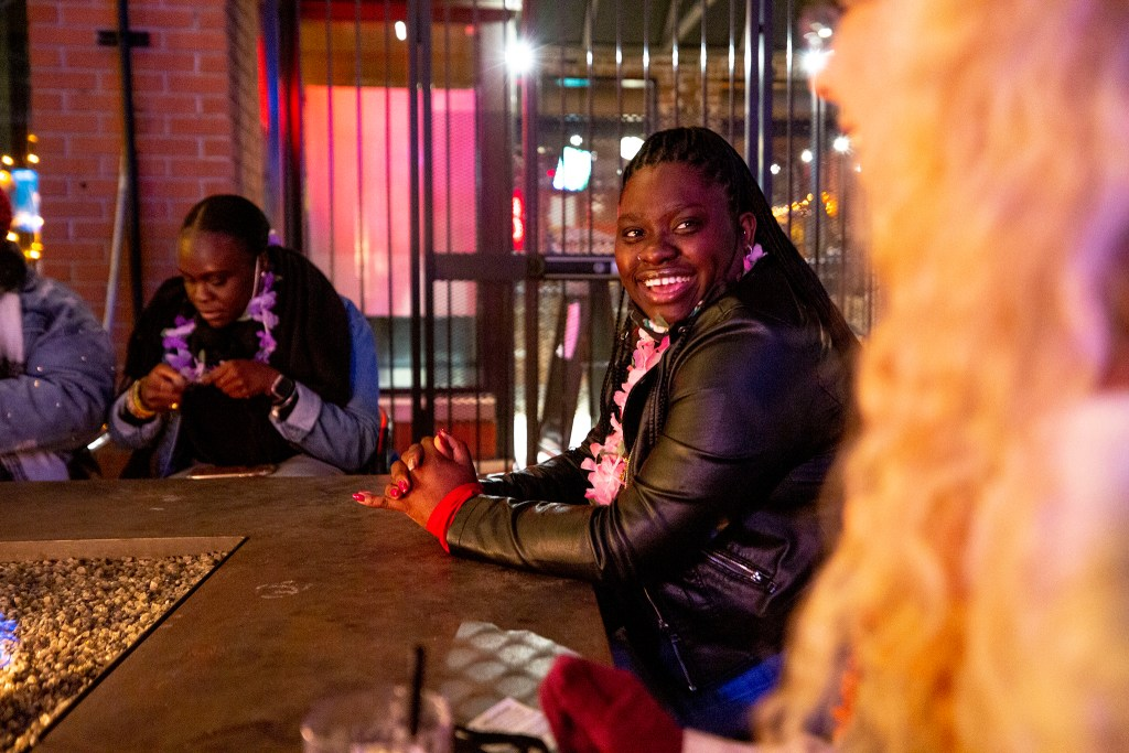 Elizabeth Ojo, who's visiting from Staten Island, strikes up a conversation with a stranger as the Denver Pub Crawl begins its LoDo tour at Brother's Bar and Grill. Oct. 23, 2020.