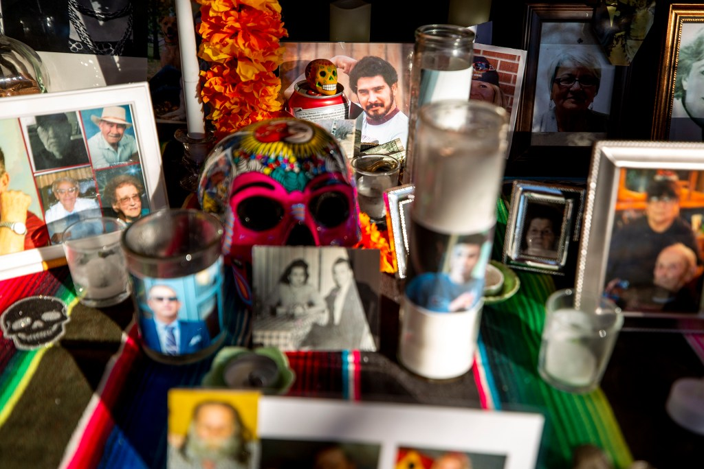 A photo of Bill Stephens, Paul's dad, peers through photos and candles packed into the ofrenda that Paul and Christopher Jorgenson built on their front porch in Harvey Park. Oct. 29, 2020.