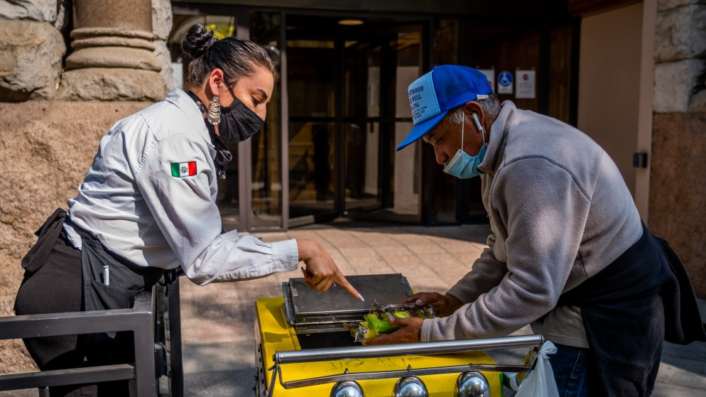 A waitress stops Delgado and picks out a paleta while he's on his way to a nearby convenience store for refreshments and a break in downtown Denver on Oct. 8, 2020. He sometimes worries about meeting so many people throughout the day during the coronavirus pandemic, but knows he must take the risk to make money to survive.