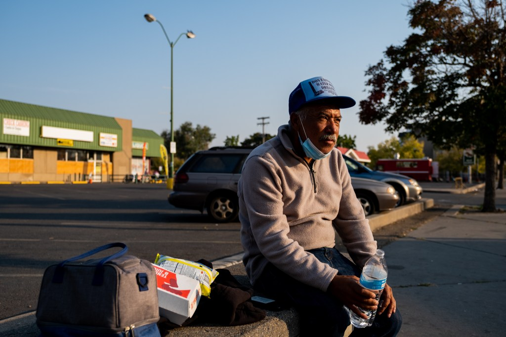 Delgado waits to ride the bus home after a more than 10 mile day of selling paletas on Oct. 8, 2020. At 58 years old, he usually showers and turns in early every evening, exhausted by the day's grueling work.