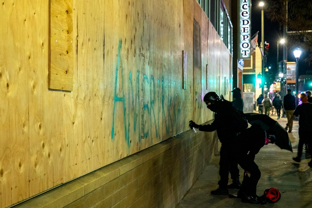 """A demonstrator writes """"Amerikkka"""" on the side of a building on East Colfax Avenue during a protest against the police and the government, regardless of who wins the election. Nov. 4, 2020."""