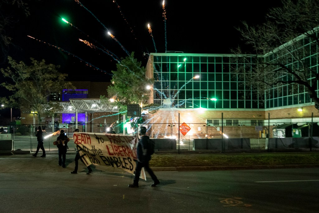 A firework explodes at Denver Police District Six headquarters, lobbed by a demonstrator protesting police and the government, regardless of who wins the election. Nov. 4, 2020.