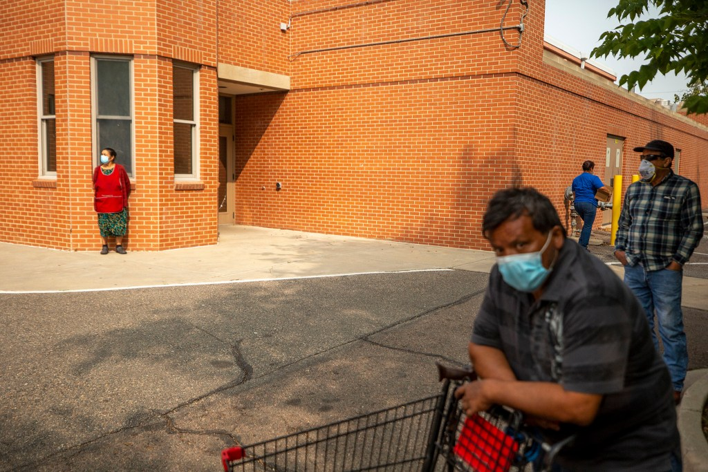 People wait in line for a food pantry set up outside Wyatt Academy in Cole. Sept. 16, 2020.
