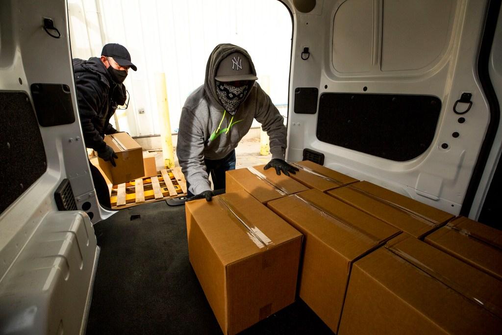Fernando Hermosillo (left) and Felipe Lopez load Bondadosa grocery boxes into a van.  December 10, 2020.