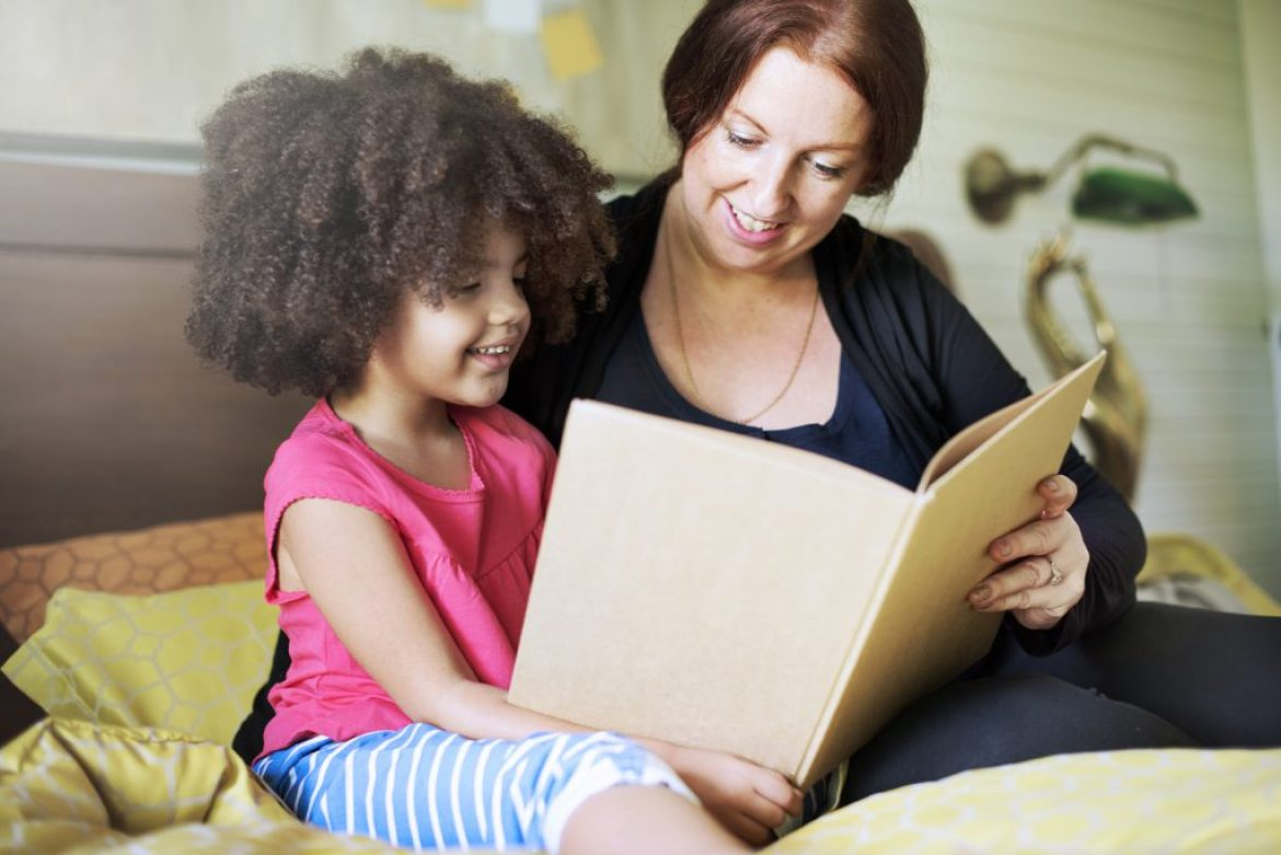 Daughter reading a book with parent