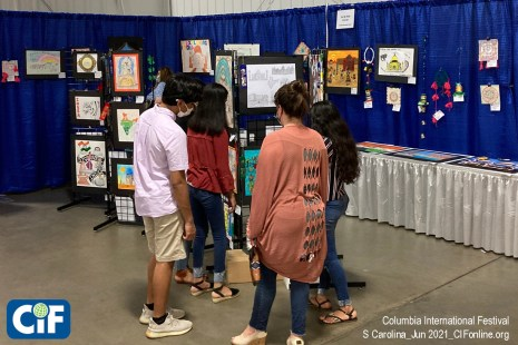 Guests enjoy looking at student Art Contest display at the Columbia International Festival.