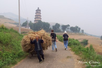 In 2005, Vivian and our colleague Josh walk toward the tower, past a man with a rather rough job description!