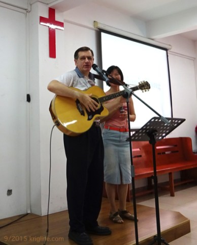 """With interpreter Faith behind me, I prepare to sing """"Vivian's song"""" at the Bridge. (The day's topic was """"how to find the perfect mate"""". Look for it at MATB.org.)"""