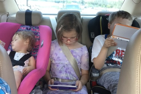I snapped this over my shoulder in the car. The youngest has fallen asleep, and the two older children are enjoying electronic games. The adults are enjoying the peace!