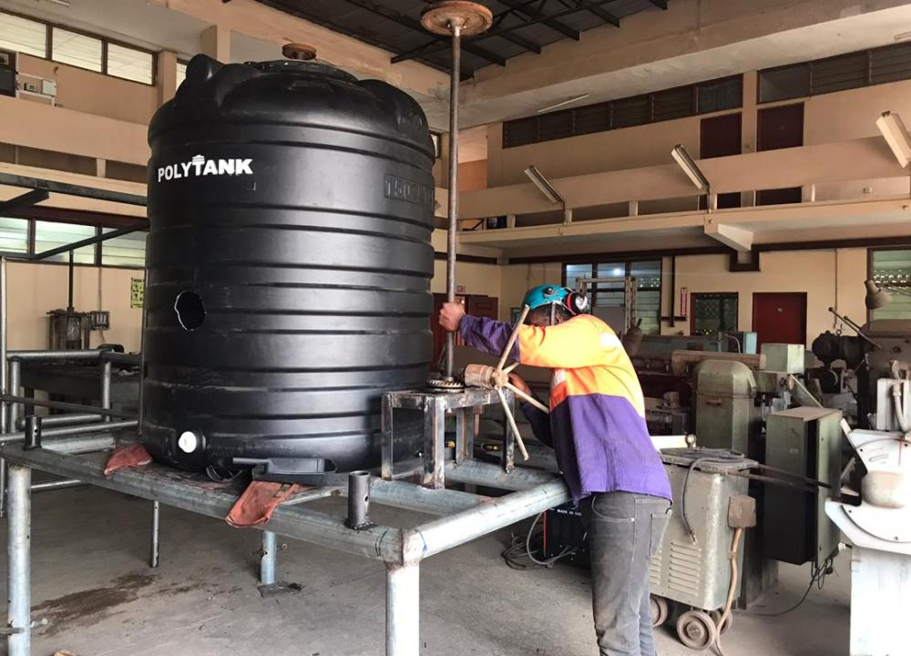 A man works on the stirrer mechanism next to the large tank