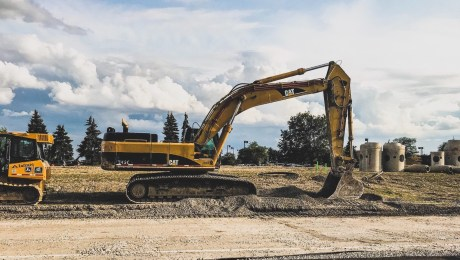 Yellow Caterpillar excavator digging up dirt.