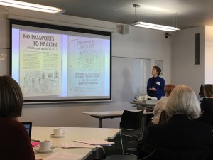 """Kitty Worthing presenting with a slide featuring an old leaflet saying """"no passports to health"""""""