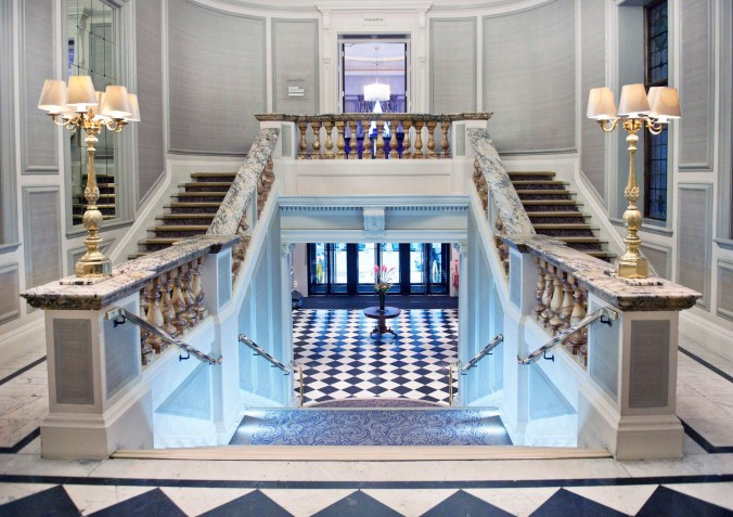 Photograph showing a perfectly proportioned and symmetrical grand stair case with marble balustrades