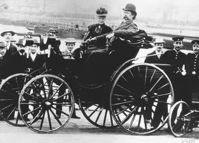 Bertha and Carl Benz sitting in one of their horseless carriages, surrounded by various onlookers.