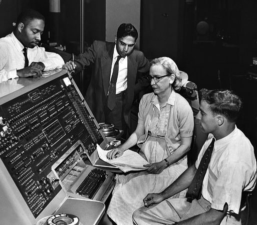Grace Hopper sits at a large 50s style computer along with three men in suits. She is holding a sheaf of papers.