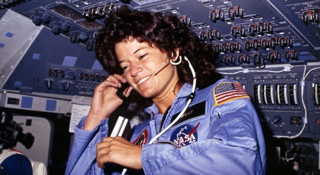 A young and smiling woman is talking into her headset wearing a blue NASA jumpsuit. She is in a small cockpit area with many switches and wires.